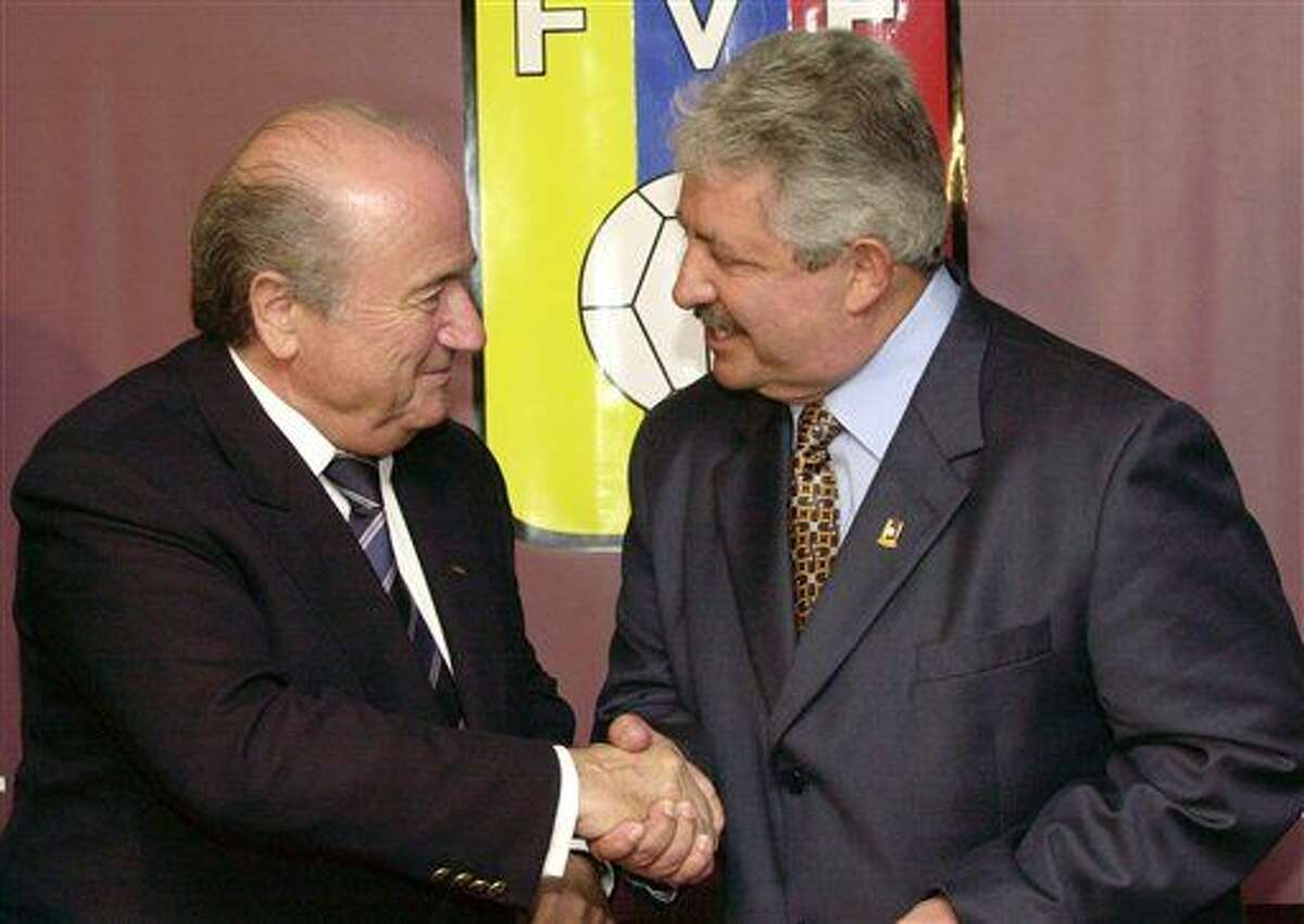 FILE - In this Nov. 8, 2004 file photo Sepp Blatter, President of the FIFA, left, shakes hands with the President of the Venezuelan Soccer Federation, Rafael Esquivel, in Caracas, Venezuela. The former president of the Venezuelan soccer federation Rafael Esquivel has withdrawn his appeal before Switzerland's highest court against extradition to the United States. Esquivel was arrested in Zurich in May amid a U.S. corruption probe that has shaken football's world governing body FIFA. A spokesman for Switzerland's Federal Office of Justice says Esquivel informed Swiss authorities of his decision Friday Feb. 26, 2016. (AP Photo/Leslie Mazoch, File)