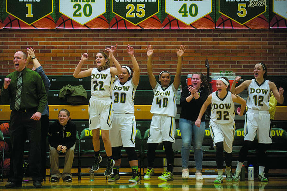 Dow High girls basketball head coach Kyle Theisen and members of the team celebrate the win over Saginaw Heritage High School 48-40 Friday night. Heritage High is ranked No. 1 in Class A for girls basketball.