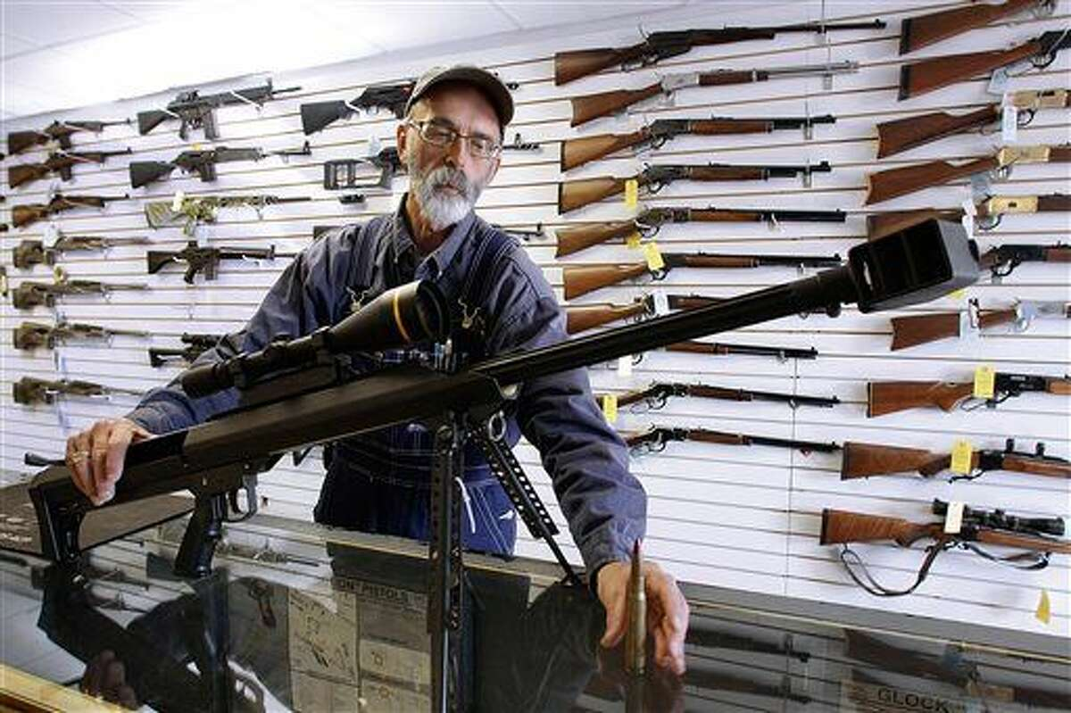 FILE - In this Dec. 4, 2008, file photo, Capitol City Arms Supply owner Steve Swartz shows off a Barrett .50-caliber rifle in Springfield, Ill. The Tennessee Senate on Wednesday, Feb. 24, 2016, gave final approval to a resolution designating the firearm as the state's official state rifle. (AP Photo/Seth Perlman, File)
