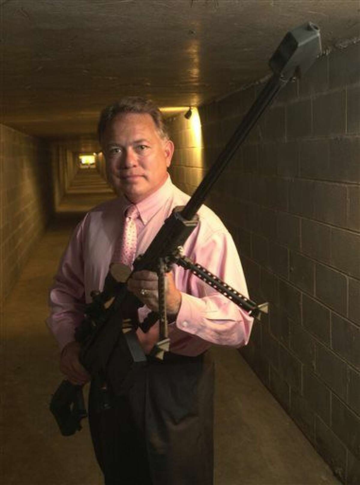 FILE - In this Oct. 21, 2005, file photo, Ronnie Barrett, founder of Barrett Firearms Manufacturing Inc., displays his company's .50-caliber rifle inside a 100 meter test-firing tunnel at his facility in Murfreesboro, Tenn. The state Senate on Wednesday, Feb. 24, 2016, gave final approval to a resolution designating the firearm as Tennessee's official state rifle. (AP Photo/Christopher Berkey, File)