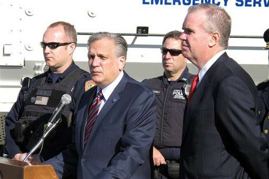 FILE- In this Nov. 16, 2015 file photo, Nassau County Executive Edward Mangano, second left, and Nassau County's acting Police Commissioner Thomas Krumpter, right, speak at a news conference in Mineola, N.Y. Mangano says he is a victim of cybercrime and is vehemently denying allegations in a TV report that he sent sexually suggestive texts to a public relations executive who has done work for the county. (AP Photo/Frank Eltman, File) Photo: Frank Eltman