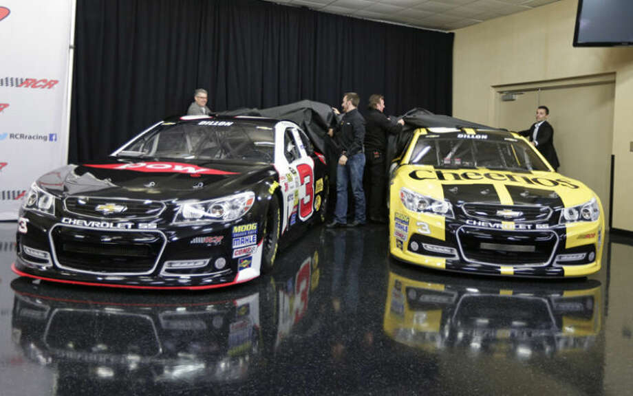 AP Photo | Chuck BurtonAustin Dillon, center left, and team owner Richard Childress, center right, help unveil the cars Dillon will drive in the 2014 NASCAR Sprint Cup series during a news conference at Charlotte Motor Speedway in Concord, N.C., today. The late Dale Earnhardt's famed No. 3 will be back on track in the elite Sprint Cup Series next season with Dillon using the number. The Dow Chemical Co. is one of two main sponsors of the cars. Photo: Chuck Burton