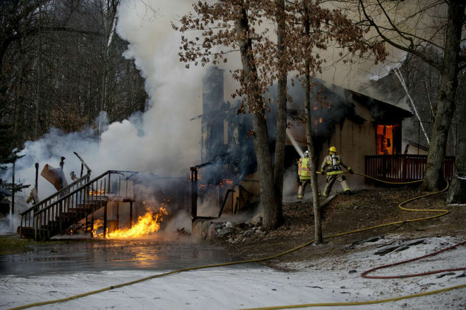 NEIL BLAKE | nblake@mdn.netFirefighters battle a blaze at a home on Huckleberry Road between 11 Mile Road and North Castor Road on Tuesday.