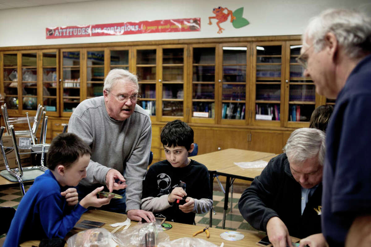"""SEAN PROCTOR   sproctor@mdn.netDennis Caney, center left, of Midland, points to a compact disc and talks with Lee Hodges, right, while helping Central Middle School sixth-graders Justin Baker, right, and Samir Ghaith build a crystal radio Wednesday afternoon during radio club. Caney started the club in 2006, and hopes that the members will come away with an interest in the sciences. """"We deal primarily with electronics and electricity, which is a little bit of physics, a little bit of chemistry and a little bit of math,"""" Caney said."""