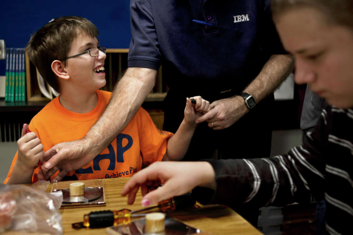 SEAN PROCTOR   sproctor@mdn.netChris Washington, a sixth-grader at Central Middle School, laughs while Lee Hodges, of Midland, helps him put together a crystal radio Wednesday afternoon.