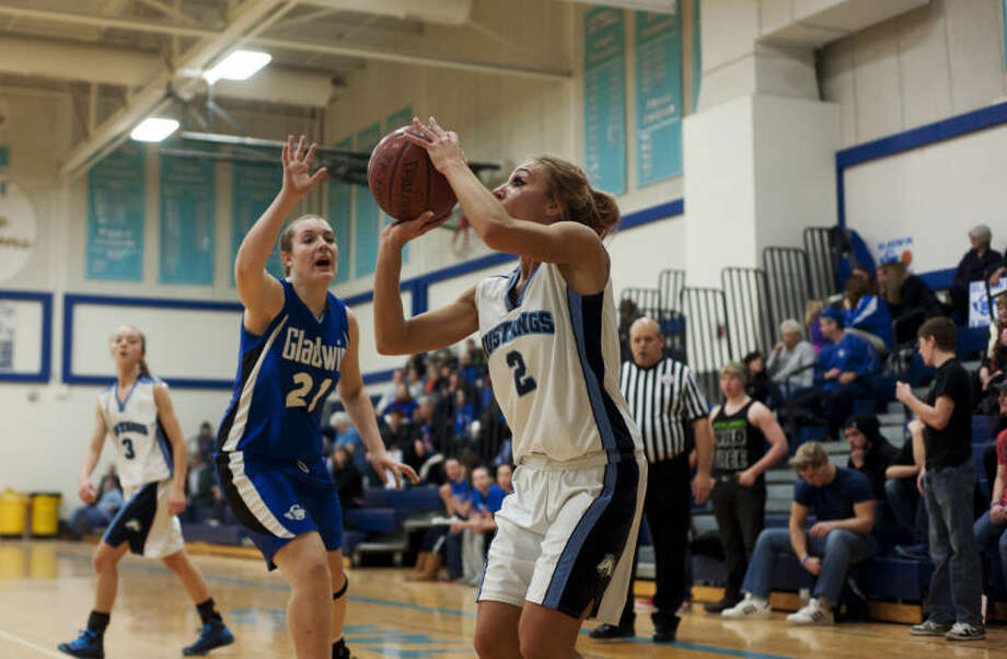 ZACK WITTMAN | For the Daily NewsMeridian's Hannah Stockford prepares for a three-point shot as Gladwin's Madison Howard attempts to block her during Meridian's game against Gladwin Thursday night.