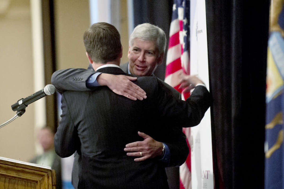 NICK KING   nking@mdn.netGov. Rick Snyder, right, hugs Michigan Attorney General Bill Schuette, R-Midland, at the Midland Area Chamber of Commerce's 74th annual meeting.