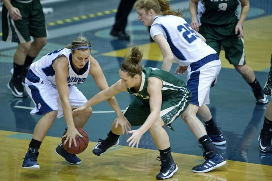 NICK KING | nking@mdn.netNorthwood's Gabrielle Rivette, left, scrambles to get the ball from Tiffin's Stephanie Kelly, right, during the first half Thursday at the Bennett Center. Northwood's Kaitlin Susan, far right, looks on. Tiffin won 59-58. Photo: Nick King/Midland  Daily News