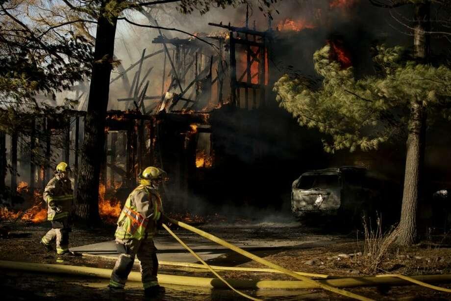 NEIL BLAKE | nblake@mdn.netA fire destroys a lakefront home in Sanford on Monday. Photo: Neil Blake/Midland  Daily News