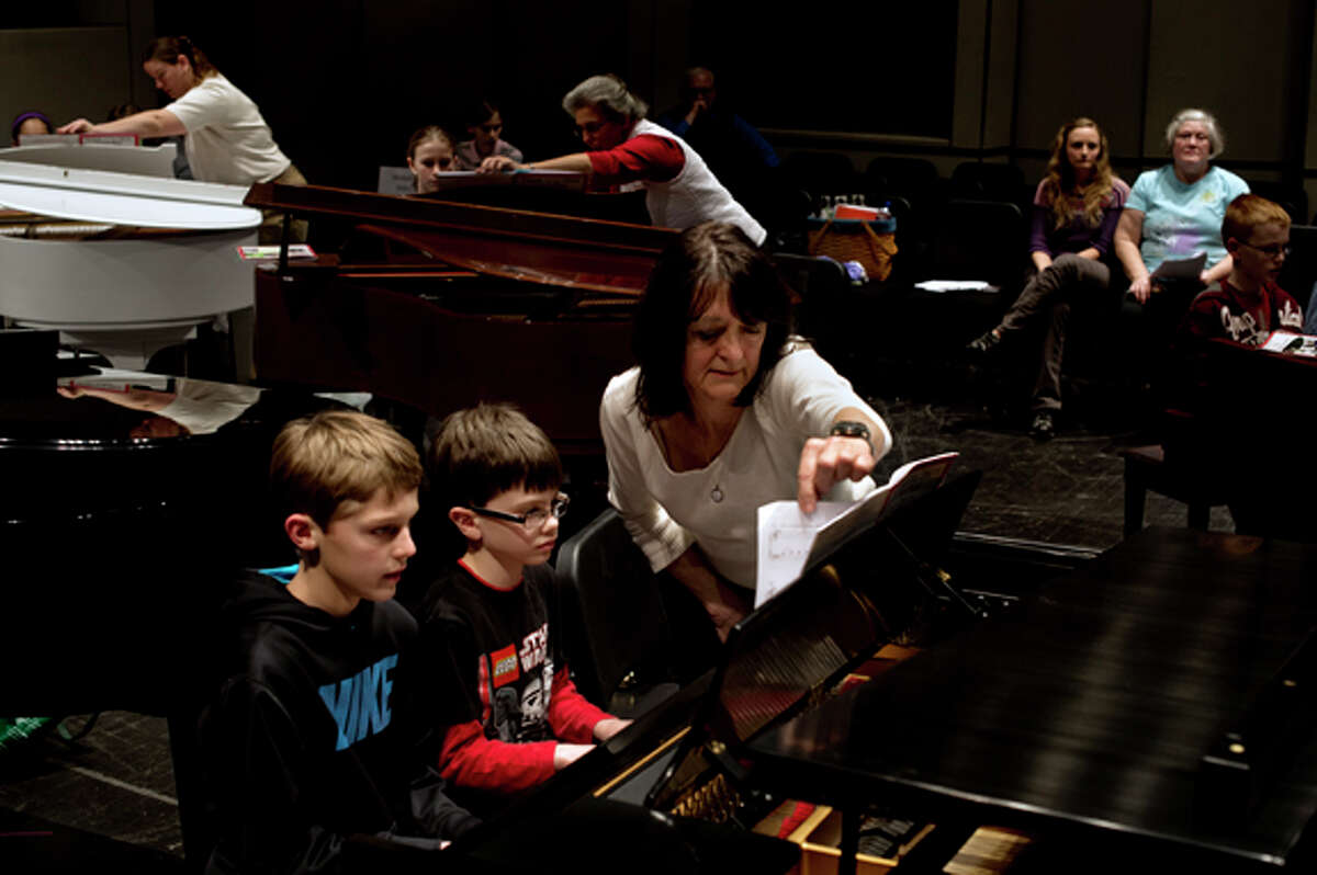 Mary Ann Anschutz, of Midland, turns over a page as Thomas Metcalf, 8, center, and Jack Miller, 10, practice their four-handed duet of The Yellow Rose of Texas Friday evening during the recital practice for KeyboardFest at the Midland Center for the Arts. Anschutz has taught piano for 40 years and been involved with KeyboardFest since the first recital, 23 years ago. Presented by the Midland Music Teachers' Association, the official recital starts at 7 p.m. Saturday and features numerous students playing the piano simultaneously.