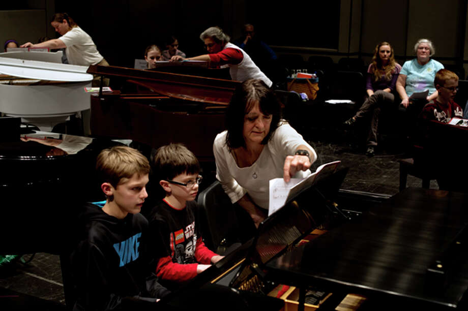Mary Ann Anschutz, of Midland, turns over a page as Thomas Metcalf, 8, center, and Jack Miller, 10, practice their four-handed duet of The Yellow Rose of Texas Friday evening during the recital practice for KeyboardFest at the Midland Center for the Arts. Anschutz has taught piano for 40 years and been involved with KeyboardFest since the first recital, 23 years ago. Presented by the Midland Music Teachers' Association, the official recital starts at 7 p.m. Saturday and features numerous students playing the piano simultaneously. Photo: Sean Proctor / (c) Sean Proctor (c) Midland Daily News