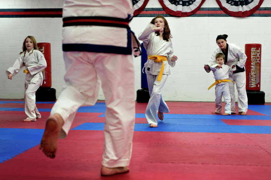 SEAN PROCTOR | sproctor@mdn.netAs Master James Hixenbaugh of Davison, foreground, guides McKenna, left, and Ryleigh Kramer, center, of Midland, through Tang Soo Do moves Summer Tanner, 21, right, of Davison, helps Caleb Haney practice the proper motions during the yellow belt class at the Professional Karate School of America on North Saginaw Road. Photo: Sean Proctor / (c) Sean Proctor (c) Midland Daily News