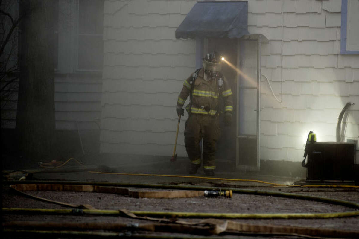 SEAN PROCTOR   sproctor@mdn.netA firefighter investigates a fire at a home on Ashman Street Tuesday in Midland. No one was hurt in the blaze. The fire was caused by the furnace in the basement.