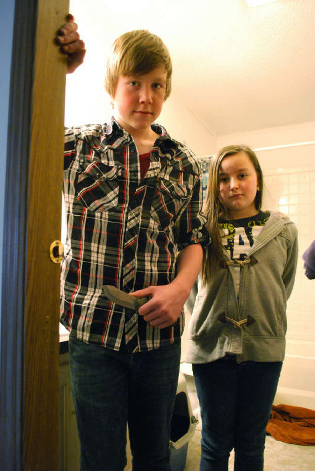AP Photo | Detroit Free Press, John CarlisleJames Persyn III, 14, holds the knife he armed himself with on Wednesday night while posing for a picture with his sister, Acelin Persyn, 11, a their Shepherd home.