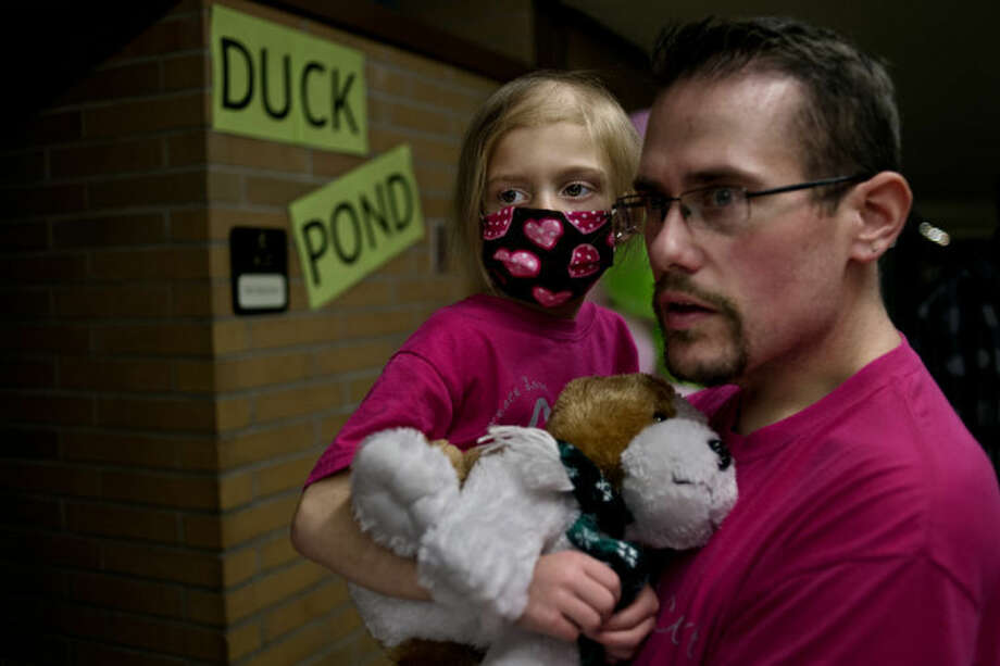"SEAN PROCTOR | sproctor@mdn.net Kurt Johns carries his daughter Katie, 5, down the hallway of Bullock Creek High School where various carnival style games were set up Friday evening during the boy's and girl's basketball game doubleheader against Shepherd High School. Creekers for a Cause, a program at the high school, set up and ran the carnival, along with a 50/50 raffle, a halftime shootout, a silent auction and sold bottles of Coca-Cola for to raise money for Katie, a Floyd Elementary student suffering from brain cancer. Since the original diagnosis and the subsequent doctors visits and, most recently, the chemotherapy treatments, the Johns said that community outreach has consistently poured in, including anonymous donations through the mail. ""It doesn't seem like thank you is enough,"" Andrea, Katie's mother, said. Another benefit is currently planned for Wednesday night during the Varsity wrestling match at the High School. Photo: Sean Proctor"