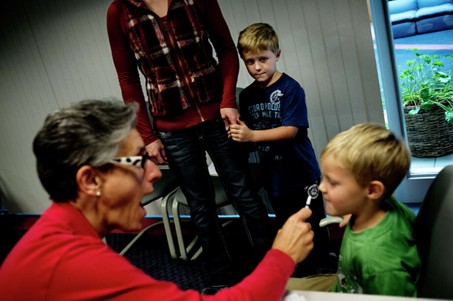 Registered nurse Laure Smith makes a face while giving Lane Zalucha, 3, of Linnwood, a flu mist as Lane's brother Beau, 5, holds onto his mother Dana's hand while waiting his turn Wednesday afternoon at the Midland County Health Department. Photo: Sean Proctor / (c) Sean Proctor (c) Midland Daily News