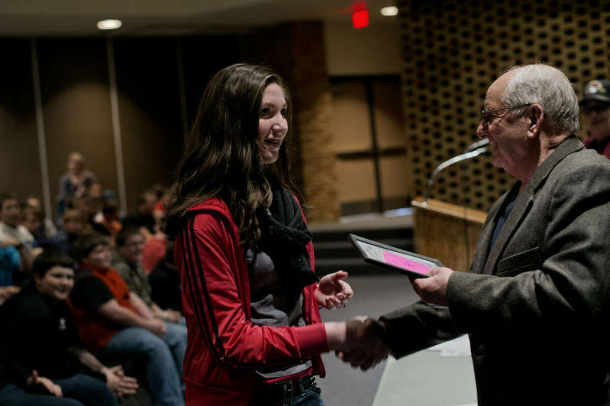 SEAN PROCTOR   sproctor@mdn.net Gene Robinson, right, the mayor of Coleman, hands a framed certificate to seventh grader Serena Rogers recognizing her second place finish in the Veterans of Foreign Wars Patriot Pen essay contest Friday afternoon at Coleman High School. Following the recognition of the essay contest winners, State Representative Kevin Cotter talked with students and answered questions, ranging from how much he made, his stance on gun control and if he preferred the University of Michigan or Michigan State University sports.
