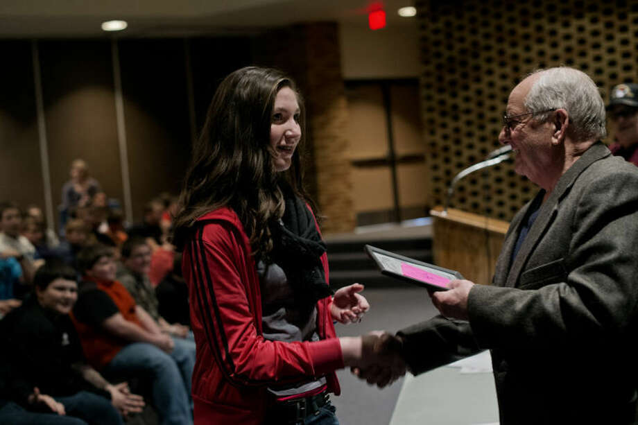 SEAN PROCTOR | sproctor@mdn.net Gene Robinson, right, the mayor of Coleman, hands a framed certificate to seventh grader Serena Rogers recognizing her second place finish in the Veterans of Foreign Wars Patriot Pen essay contest Friday afternoon at Coleman High School. Following the recognition of the essay contest winners, State Representative Kevin Cotter talked with students and answered questions, ranging from how much he made, his stance on gun control and if he preferred the University of Michigan or Michigan State University sports. Photo: Sean Proctor