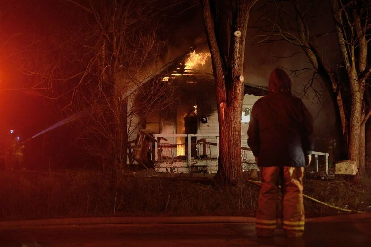 SEAN PROCTOR   sproctor@mdn.netFirefighters from Mills, Larkin and Hope townships combat a blaze at 5945 N. Sturgeon Road Monday night.