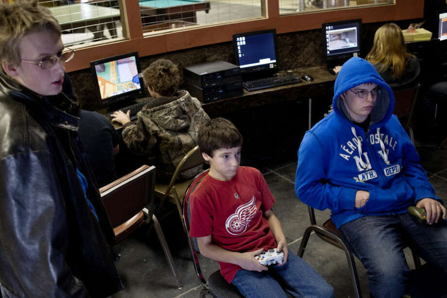"SEAN PROCTOR | sproctor@mdn.netNolan Kennedy, center, 12, of Midland, plays Call of Duty: Black Ops 2 while Zac Smith, 15, right, and Michael Tiffany, 18, look on Wednesday afternoon in ""The CAGE"", The ROCK Youth Center's new computer and gaming room. ""The CAGE"" stands for ""Computer and Gaming Experience,"" and features seven computers, a big screen TV and an Xbox 360. The computers and gaming system were purchased through a grant from IBM. ""It's pretty sweet. I get to play all of my favorite games,"" Kennedy said. Photo: Sean Proctor"