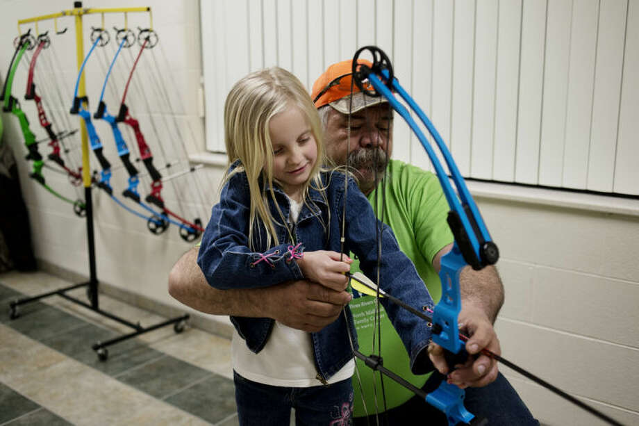NEIL BLAKE | nblake@mdn.netBill Sutherland of Midland helps Abrielle Barko, 7, of Midland, draw back a bow at Call of the Wild Fundraiser at the North Midland Family Center on Friday. The annual event gave the center a chance to showcase some of the activities they offer while raising money for the center. This spring archery classes will be offered at the NMFC on Wednesday evenings from March 6 through April 24 for children ages 7 and up. Photo: Neil Blake/Midland  Daily News