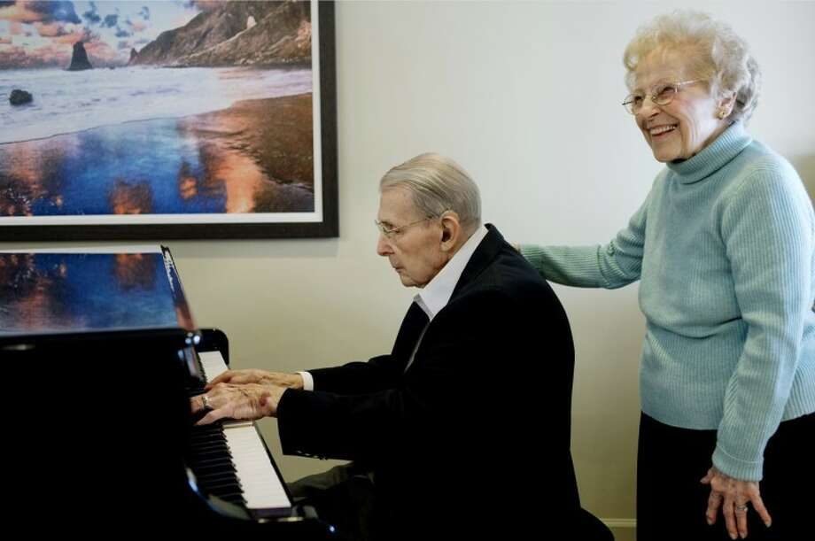 "NICK KING | nking@mdn.netLouis Wirth, left, plays a song on the piano as his wife, Helen, stands next to him Friday in the lobby of the Abbey Park retirement center in Grand Blanc. ""I like to play the old songs,"" said Louis of his musical talents. Louis and Helen are celebrating their 77th wedding anniversary on New Year's Day. The two lived in Midland for 40 years before moving the Abbey Park retirement center. Louis retired from Dow in 1981 after 50 years of service."