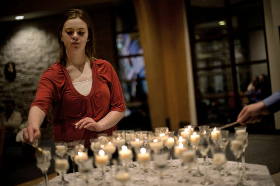 "SEAN PROCTOR | sproctor@mdn.netSamantha Feldotte, 19, of Saginaw, puts out a candle along with Scott Campell (not pictured), during the candle snuffing ceremony during the ""40 Years of Tears"" memorial vigil Tuesday evening at St. Agnes Catholic Church in Freeland. Photo: Sean Proctor"