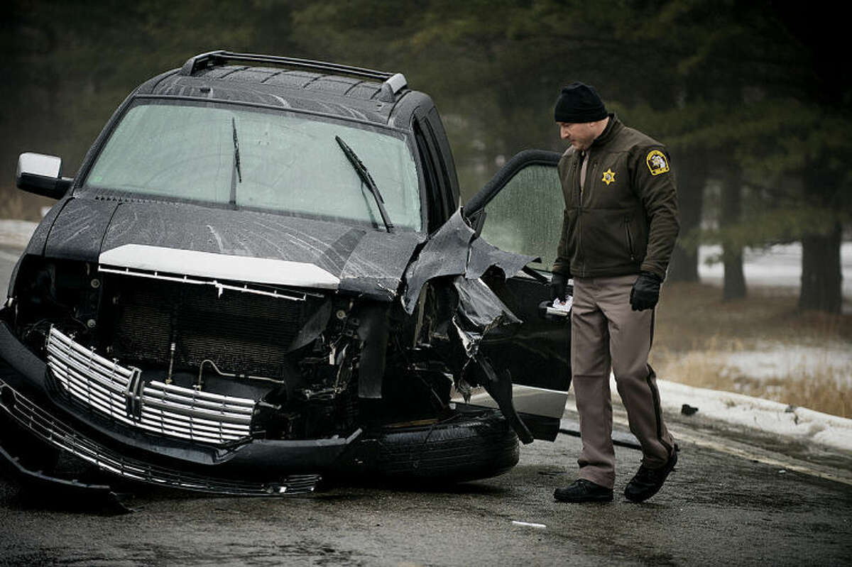 NEIL BLAKE   nblake@mdn.netMidland County Sheriff Scott Stephenson looks at a Lincoln Navigator that was involved in an accident with a liquid propane tanker truck on South Eight Mile and Stewart Road. The accident caused the evacuation of some residents on Tuesday.