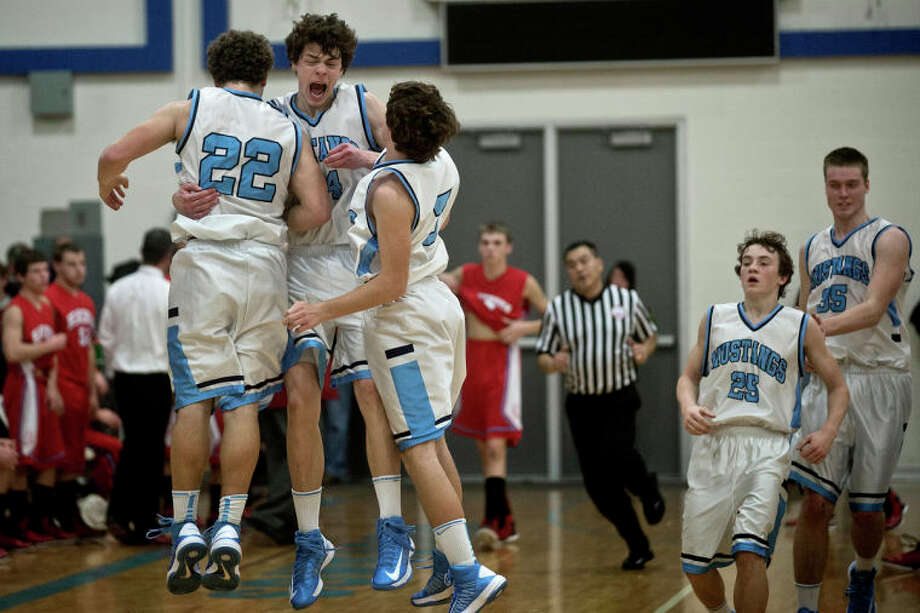 SEAN PROCTOR | sproctor@mdn.netMeridian's Kevin Scheibert celebrates with his teammates Zack Arthur and Charles Ellithorpe after time expires against Beaverton Wednesday night at Meridian High School. The Mustangs beat the Beavers 45-40 to remain undefeated on the season. Photo: Sean Proctor / (c) Sean Proctor (c) Midland Daily News