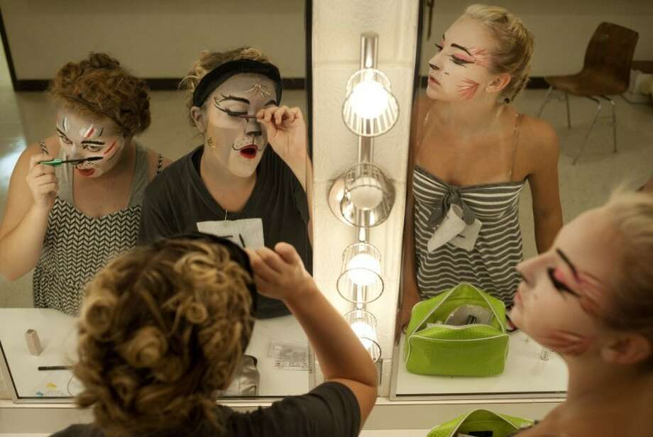 """BRITTNEY LOHMILLER   blohmiller@mdn.netFrom left, Emma Moore, 17, of Midland, Kaila Smith, 17, of Sanford, and MacKenna Hartman, 15, of Midland, put on false eyelashes after having their faces air brushed to look like characters in the musical """"Cats."""" The 31-member Teenage Musical Inc. cast performed in August. Photo: Brittney Lohmiller"""