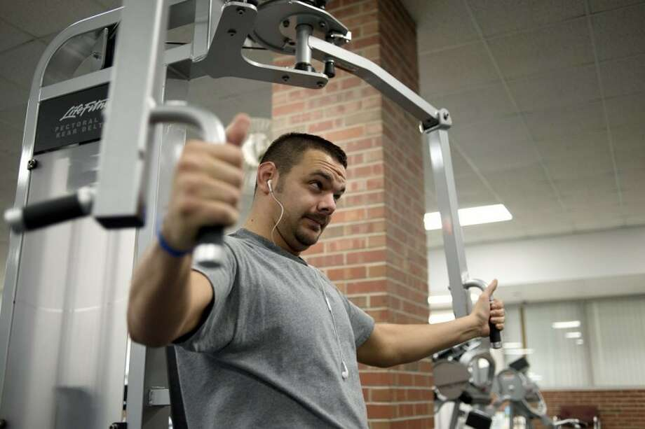 NICK KING | nking@mdn.net Jon Klein works on his chest during a workout session on Wednesday at the Midland Community Center. Klein, who has been coming to the gym regularly for a year, has seen many improvements to his health since starting his routine. Photo: Nick King/Midland  Daily News