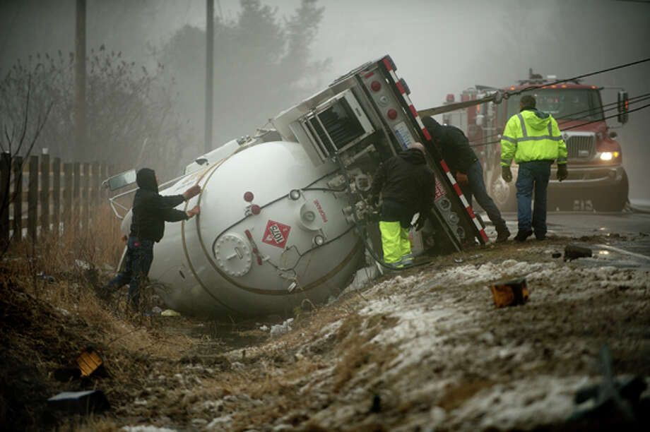 """Workers from Beehr's Towing secure straps to an overturned liquid propane gas tanker truck on South Eight Mile near Stewart Road on Tuesday. The accident involved a Lincoln Navigator and the tanker caused the evacuation of residents within one-half mile of the crash. Residents could choose to stay in their home if they wished as the site was cleared. Gordon Swinson, whose yard the tanker crashed in, called 911 after hearing the crash. """"It sounded like a roll of thunder,"""" he said. Photo: Neil Blake/Midland  Daily News / Midland Daily News"""
