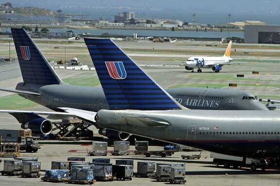A pair of United Airlines' Boeing 747's are parked at the international terminal as a United Airlines' Ted airplane passes in the background at San Francisco International Airport in a file photo from June 22, 2005. While United Airlines is about to emerge from more than three years of bankruptcy reorganization, two of its biggest rivals, Delta and Northwest, are still in the early stages of restructuring their own finances under Chapter 11. (AP Photo/Eric Risberg, File)
