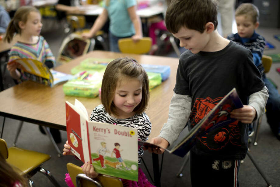 NICK KING | nking@mdn.net Plymouth Elementary kindergartner Trevor Murphy, right, shows off his book to classmate Emma Bornemann during class on Wednesday in Jenni Lyon's class. Photo: Nick King/Midland  Daily News
