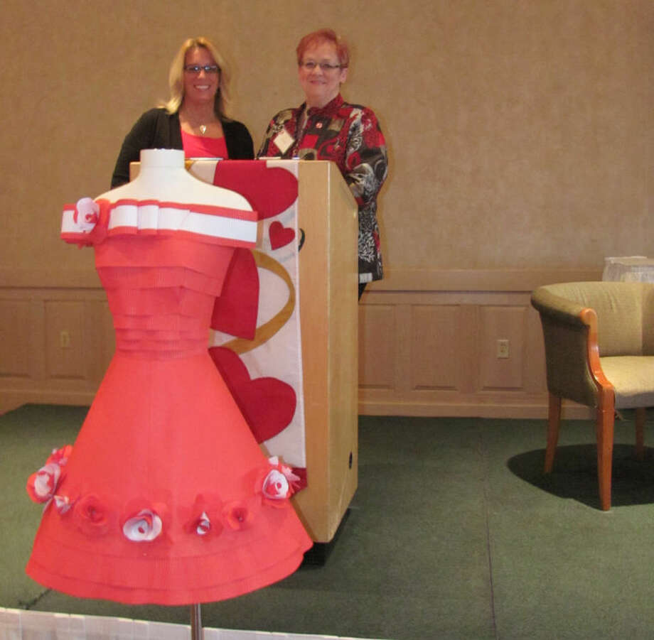 Hilary Farrell | for the Daily NewsMidland residents Denise Hus, left, and Diane Bristol stand at a podium after sharing their survivor stories to more than 200 attendees at the American Heart Association's Go Red for Women fundraising event at Freeland's Apple Mountain Conference Center.