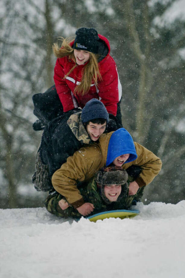 NICK KING | nking@mdn.netFrom top to bottom, Midland High School juniors Alyssa Reder, Shelden Dice, Jordan Lepley and Brett Bassage pile on one sled as they head down the hill at Midland City Forest Thursday. Photo: Nick King/Midland  Daily News
