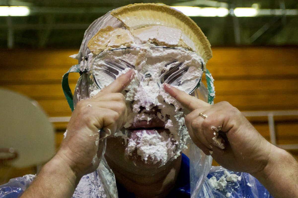 ZACK WITTMAN   For the Daily News Coleman resident Jerry Falor, a History and Government teacher at Coleman High School, uses his fingers as windshield wipers to clean his goggles after being hit with a pie thrown by a student during a student organized pie throwing assembly to raise money for the Anti-Bullying club at Coleman High School on Thursday afternnon. Anti-bullying videos were made by each class and shown during the assembly while students were randomly selected to throw pies at teachers.
