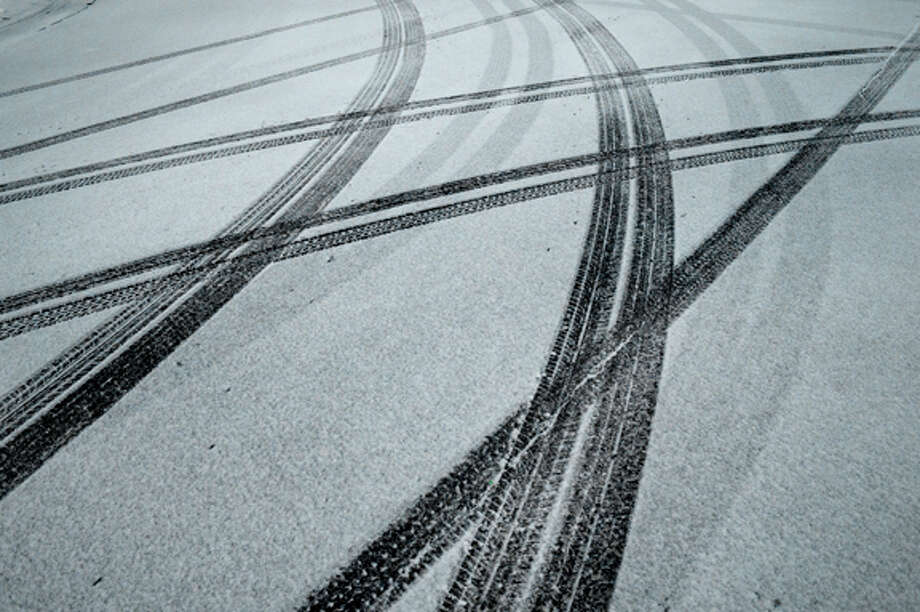 NEIL BLAKE | nblake@mdn.net Tire tracks were left in fresh snow on Thursday evening at the corner of McDonald Street and Ann Street. Snow began to fall near sunset on Thursday blanketing the county with almost a foot of snow. Photo: Neil Blake/Midland  Daily News / Midland Daily News