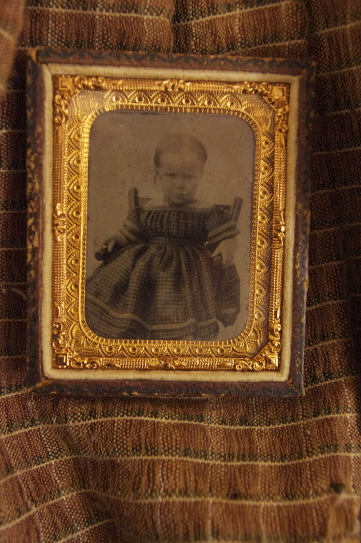 Stuart Frohm | for the Daily NewsJanie Gardner's father carried this framed image of her during the Civil War. In the image, donated to the Midland County Historical Society in the 1950s by Edith Garner Kelly, the child is wearing the dress on which the framed photo rests.