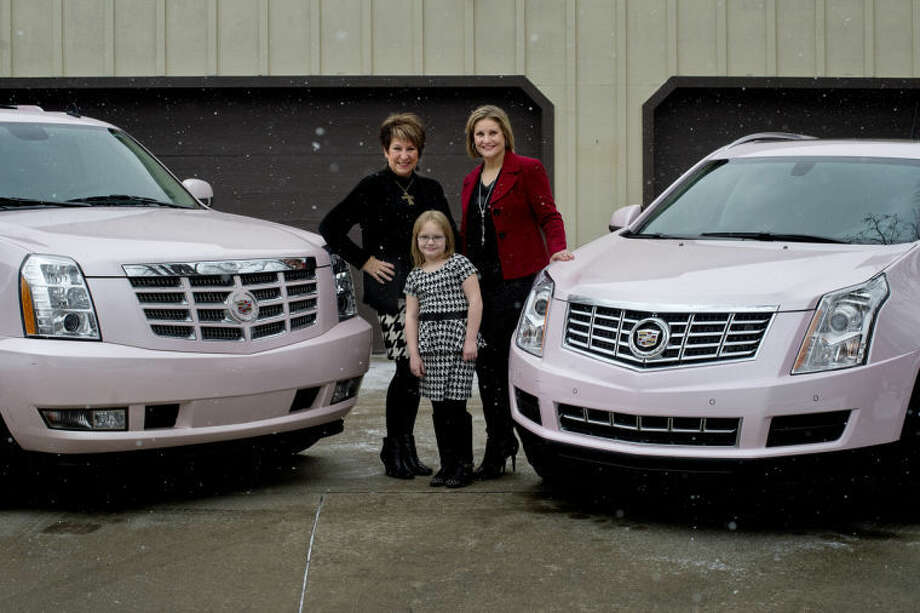 NICK KING | nking@mdn.netJudy Kawiecki, left, her grandaughter, Brynn Hansen, 6, and Brynn's mother and Judy's daughter, Lisa Hansen, pose by their pink Cadillacs which they earned the opportunity to drive based on their team production within Mary Kay. Photo: Nick King/Midland  Daily News