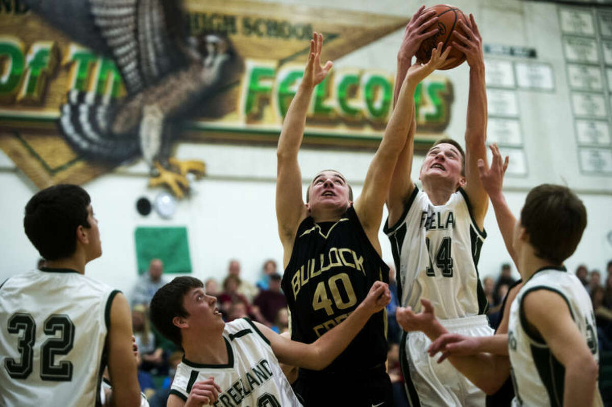 JAKE MAY   for the Daily NewsBullock Creek's Brandt Gaffke, center left, reaches to fight for possession of a rebound with Freeland's Jacob Whitting on Tuesday night at Freeland High School. The Falcons defeated the Lancers 58-45.