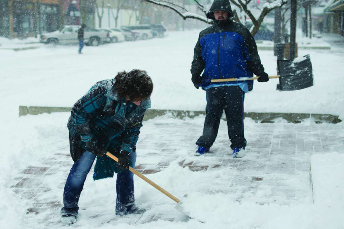 NEIL BLAKE | nblake@mdn.netConnie Servis shovels snow with Ryan Rolfe in front of Journeys Coffee House in downtown Midland on Friday.