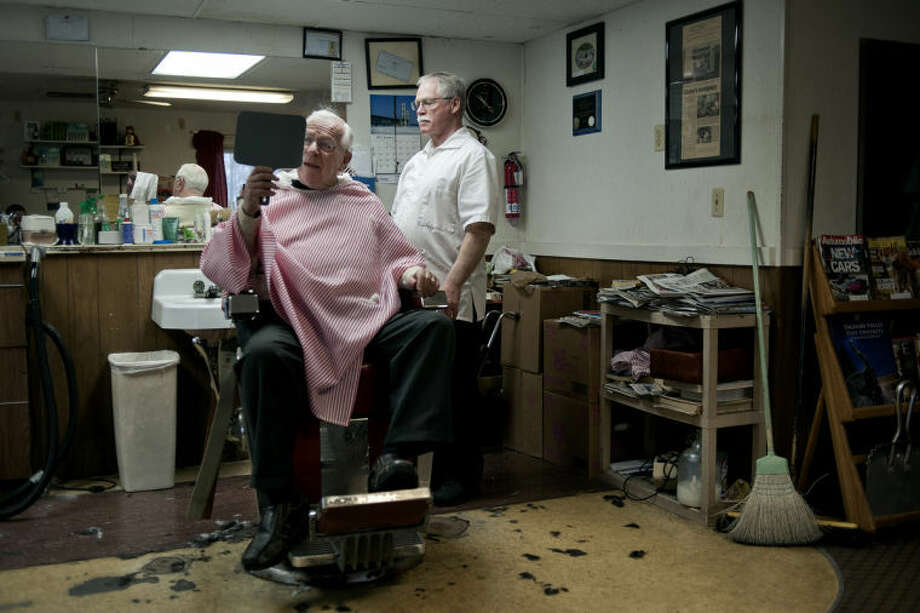 NICK KING | nking@mdn.netMichael L. Hopkins, right, looks on as his customer Robert Rhead, left, checks out his haircut in the mirror at Irish's Barber and Hairstyling in Midland. Photo: Nick King/Midland  Daily News