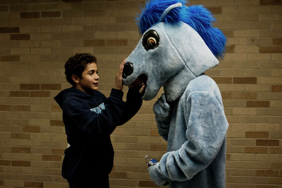 Meridian High School freshman Justin Hibbs pats the nose of his high school mascot, the Mustang, being worn by freshman Josh Gingery during the basketball game between Meridian and rival Clare on Friday. Photo: Neil Blake/Midland  Daily News / Midland Daily News