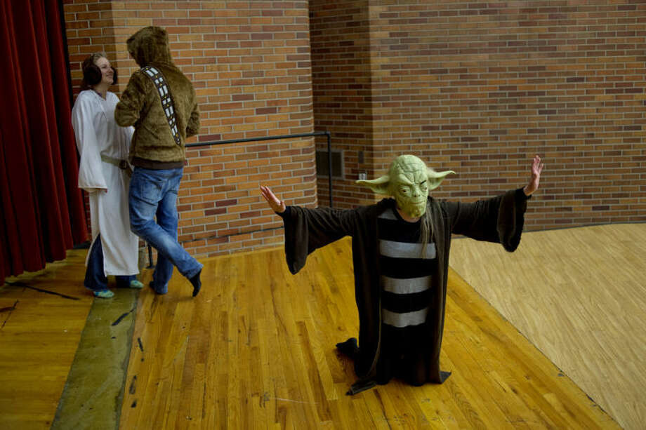 NICK KING | nking@mdn.netSeniors Clare Hyde, right, dressed as Yoda, Hannah Piper, left, dressed as Princess Leia, and Mark Gorte, center, dressed as Chewbacca, practice their emcee routine for Ren Fair. The three, along with two fellow seniors, will perform a Star Wars/Disney-themed comedy skit and introduce each act throughout the performance. Photo: Nick King/Midland  Daily News