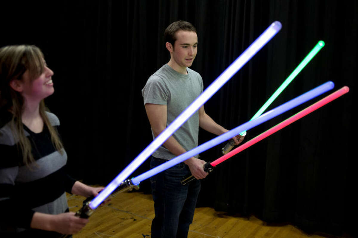 NICK KING | nking@mdn.netSeniors Billy Schuette, right, and Clare Hyde play with light sabers during their emcee practice for Ren Fair.