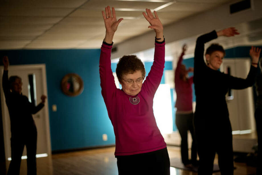 SEAN PROCTOR | sproctor@mdn.netKaren Burow stretches during her yoga class at Creative 360. Photo: Sean Proctor