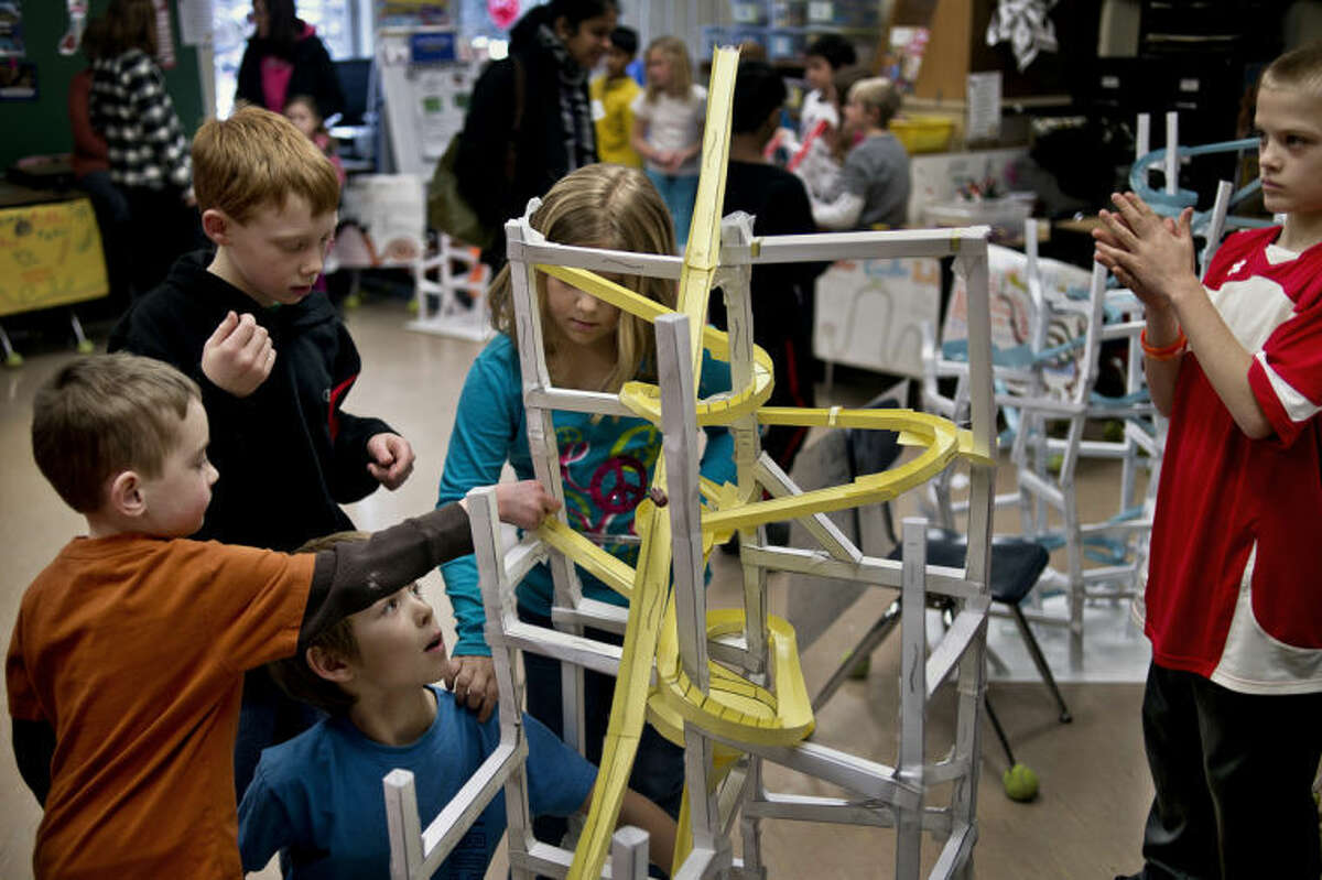 """SEAN PROCTOR   sproctor@mdn.netAiden Glumn, far left, a first-grader in Lori Kraut's class, examines the roller coaster assembled by Nate Thornton, Austin Kepsel, Emily Mackenzie and John Hine for Beth Curtis' third grade science class during """"Cedar Point Open House"""" at Adams Elementary. Third-graders from three science classes built the roller coasters out of card stock as a culminating activity for their unit on motion. Students and parents filed in through the three classrooms to see the roller coasters in action."""