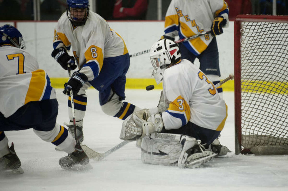 NICK KING   nking@mdn.netMidland goalie Colin Walters, right, deflects a Heritage shot as teammates Ryan Singer, left, and Elliot Digison, center, look on during the second period Wednesday at the Midland Civic Arena. Heritage won 3-2.