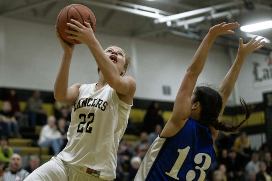 SEAN PROCTOR | sproctor@mdn.netBullock Creek's Halee Nieman goes up for a layup against Hemlock's Hannah Massa Monday night at Bullock Creek High School. The Lancers defeated the Huskies 70-42. Photo: Sean Proctor/Midland  Daily News
